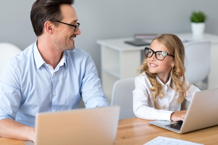 Good job. Ecstatic mature man looking at the delighted little girl while working with her on the laptops and sitting at the table
