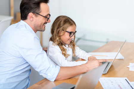 talented: Look at the screen. Confident man with glasses showing how to use a laptop to her little talented girl while sitting at the table