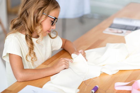 Time flies. Concentrated little lady with glasses sewing a new dress while sitting at the table