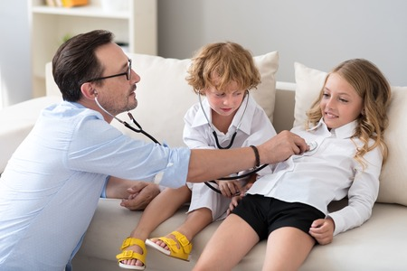 stethoscope boy: Do not laugh. Mature man examining his daughter with stethoscope while a little serious boy helping him