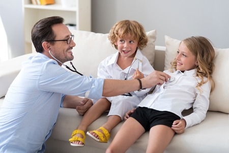 stethoscope: Your heart works. Delighted bearded man examining his smiling daughter with a stethoscope while little boy sitting near them and talking Stock Photo