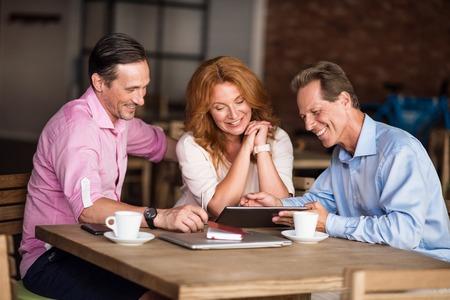 informal: Workforce. Smiling and cheerful coworkers having informal meeting in a cafe
