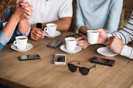 keep in touch: Keep in touch. Close up of table with cups of coffee, mobile phones and sunglasses on it Stock Photo