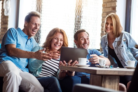 laughable: Laughable. Smiling and positive group of people using digital tablet together while drinking coffee in cafe Stock Photo