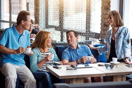 personas comunicandose: Tema del día. Feliz y contento grupo de personas que se comunican, mientras que beber juntos el café en café