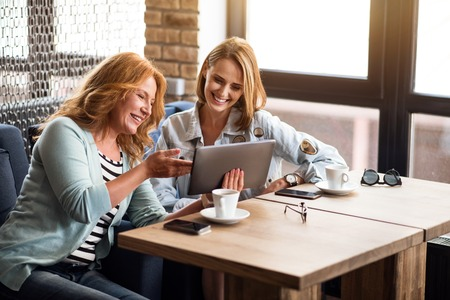 merry time: Time to gossip. Two smiling and merry woman using tablet while sitting at the table and drinking coffee