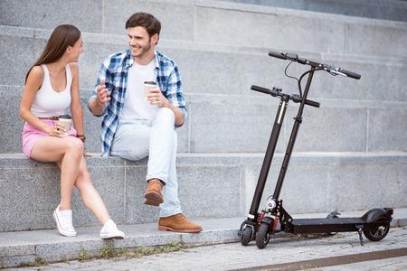 휴식을 취하다. 스쿠터가 근처에 서있는 동안 발자국에 앉아서 커피를 마시고있는 쾌활한 웃으면 서 즐거운 친구들