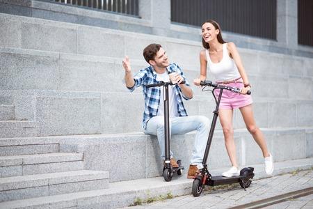 乗ってをいます。陽気な笑みを浮かべて友達が喜んでスクーターに乗って、楽しみながら一緒に休憩 写真素材