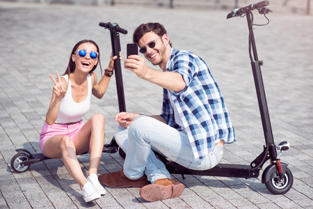 say cheese: Say cheese. Positive content smiling friends sitting on the scooter and making selfies while having fun together Stock Photo