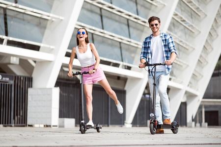 アクティブなライフ スタイル。乗って陽気な喜んで笑顔お友達一緒に屋外休憩中のスクーターをキックします。
