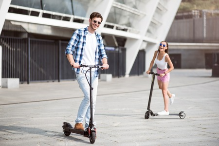 Full of joy. Positive smiling friends riding kick scooter and expressing positivity while resting outdoors