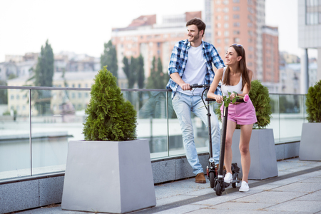 Nice view. Positive content smiling friends looking aside and riding kick scooter while resting together Stock Photo