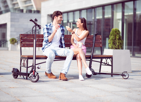 overjoyed: Help yourself. Overjoyed delighted smiling friends sitting on the bench and eating doughnuts while resting Stock Photo