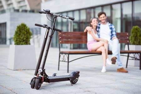 활동적인 날 이후에 쉬어 라. 바닥에 서 서 킥 스쿠터의 선택적 포커스 동안 백그라운드에서 벤치에 앉아 긍정적 인 미소 커플