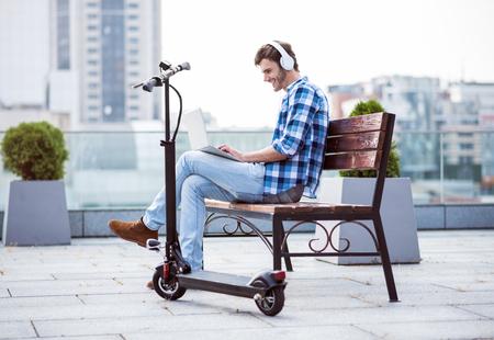 좋은 분위기에서. 긍정적 인 내용 웃는 남자 벤치에 앉아 노트북을 사용 쉬고