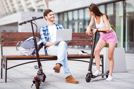 Glad to talk with you. Cheerful beautiful smiling woman riding a kick scooter while talking with her friend who is sitting on the bench
