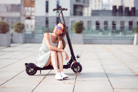 Have a break. Joyful beautiful woman smiling and sitting on the kick scooter while resting Imagens