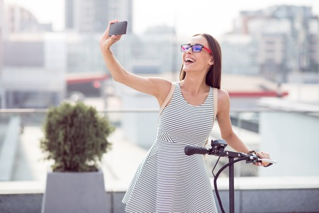 expressing joy: Full of gladness. Positive delighted smiling woman holding kick scooter and expressing joy while making selfies Stock Photo