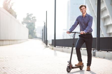 新しい根を発見します。笑っている陽気なハンサムな男とホールディング キック スクーター乗りに行っている間
