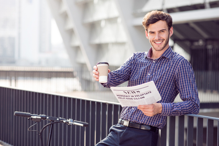 expressing joy: Get energized. Positive content handsome man drinking coffee and holding newspaper while expressing joy