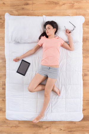 nightwear: My carrier. Top view of tired young woman wearing nightwear, sleeping on her back on bed with digital tablet and eyeglasses Stock Photo