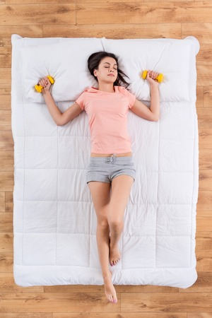 My body. Top view of pleasant young woman relaxing and sleeping on white bed having dreams of sexy body holding dumb bells in hands