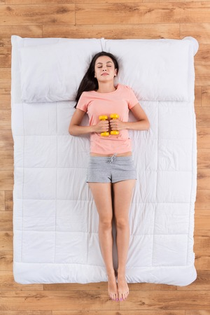 nice body: Future muscles. Top view of cheerful young woman relaxing and sleeping on white bed having dreams of nice body holding dumb bells in hands