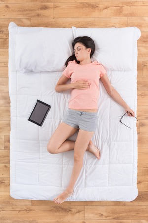 nightwear: Always connected. Top view of tired young woman wearing nightwear, sleeping on her back on bed with digital tablet and eyeglasses dreaming about future job Stock Photo