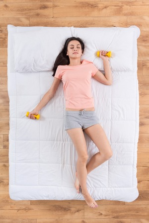 nice body: Sporty one. Top view of positive young woman sleeping on white bed dreaming about nice body holding dumb bells in hands