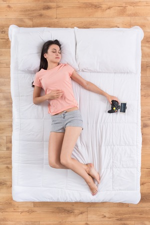 joypad: Gamer. Top view of nice young woman sleeping on back on white bed with joypad in hands and dreaming about winning in computer games Stock Photo