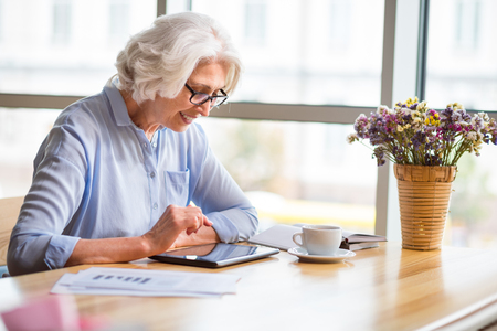 Modernize your outlook. Positive delighted senior woman smiling and using tablet while sitting at the table Stock Photo