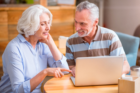 Here it is. Positive delighted senior couple sitting at the table and using laptop while resting together Stock Photo