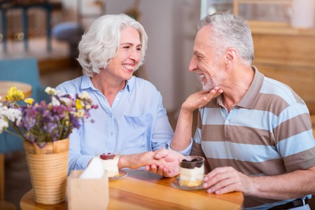 Sincere relations. Cheerful delighted senior couple expressing love and sitting at the table while resting in the cafe Stock Photo