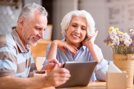 素晴らしい時間があります。喜んでうれしそうな年配のカップルして、テーブルに座って一緒に休んでいる間タブレットします。