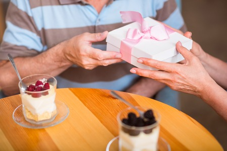 Made with love. Pleasant senior loving couple sitting at the table and holding present while having a little celebration