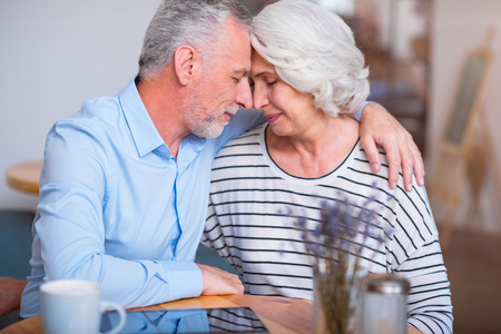 express feelings: Eternal love. Pleasant delighted senior couple sitting at the table and bonding to each other while expressing love