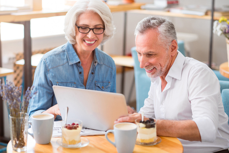 Our leisure time. Joyful delighted senior couple smiling and using laptop while resting in the cafe