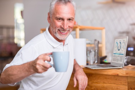 Join me. Positive delighted senior man smiling and drinking coffee while resting I the cafe