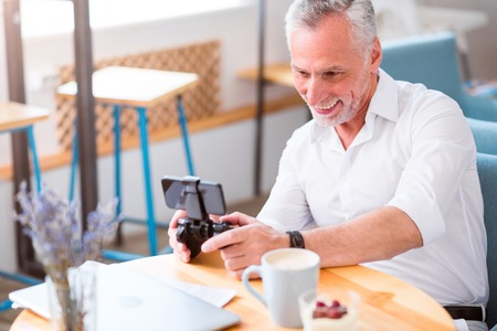 game console: Involved in play. Cheerful senior man holding game console and playing while sitting at the table in the cafe Stock Photo