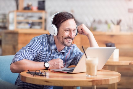 relatives: Happy to see you. Positive and smiling man communicating with his relatives using laptop and headphones