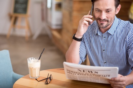 Can not believe in it. Cropped image of smiling and positive man talking per smart phone and reading newspaper Stock Photo