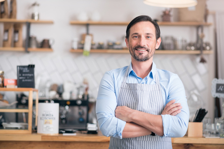 Own business. Successful cheerful small business owner standing with crossed arms Standard-Bild