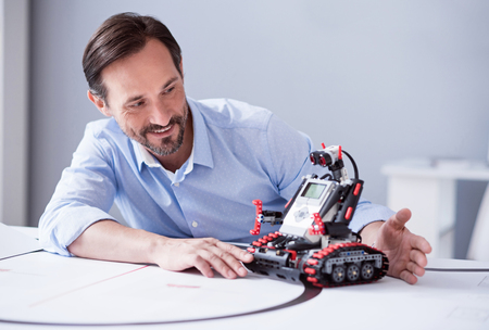 Robots à la vie quotidienne des gens ordinaires. Un homme souriant curieusement observant une machine