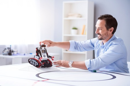 Enjoyable work. Good looking man testing a robot he created at his work place