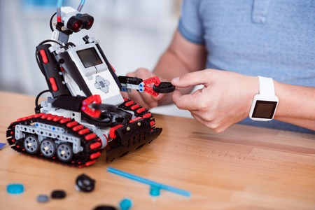 constructing: Involved in process. Pleasant man sitting at the table and constructing robot while using it Stock Photo