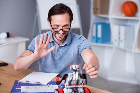 diligente: Mi criatura. hombre encantados positiva sentado en la mesa y las pruebas del robot mientras se trabaja en su proyecto