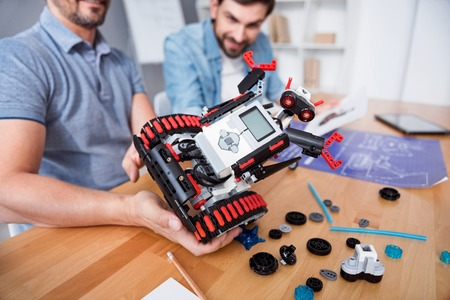 Our result. Selective focus of robot in hands of pleasant engineer holding it while sitting at the table and working with his colleague Stock Photo