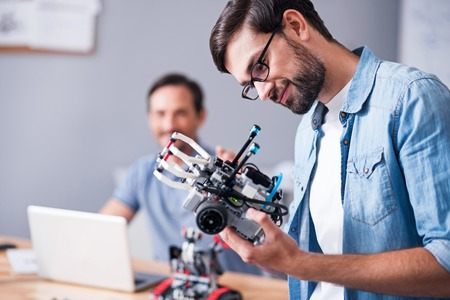 rely: Rely on technologies. Positive professional man holding robot and testing it while his colleague using laptop in the background Stock Photo