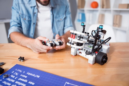 emote: Upgraded technologies. Pleasant professional man sitting at the table and holding remote control while testing robot Stock Photo