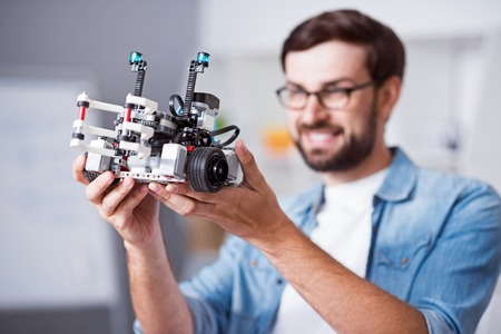 gladness: Express you emotion. Selective focus of robot in hands of positive smiling man holding it while expressing gladness